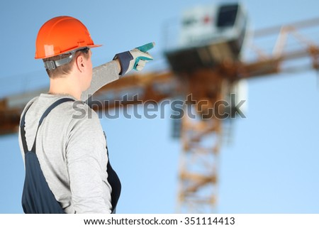 Worker in a construction site showing on a crane - stock photo
