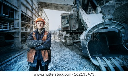 worker in a helmet stands near a big excavator crossed arms - stock photo