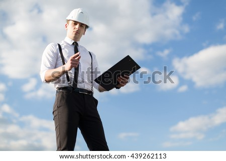Worker in a helmet with a folder in his hands - stock photo