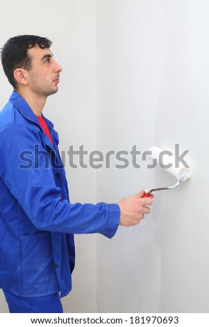 Worker in blue clothes paints by paint roller in new apartment - stock photo
