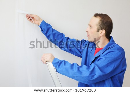 Worker in blue clothes works with painting fiberglass in new apartment - stock photo