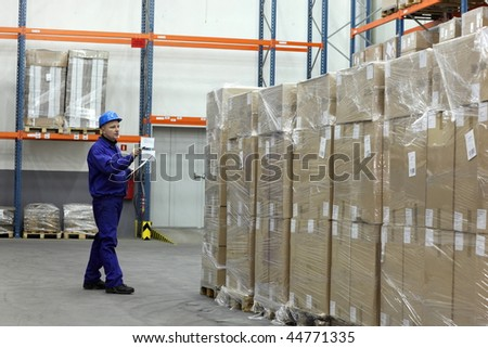 worker in blue uniform counting stocks in warehouse - stock photo