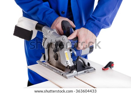 Worker in blue uniform cutting laminate with circular power saw, isolated on white - stock photo