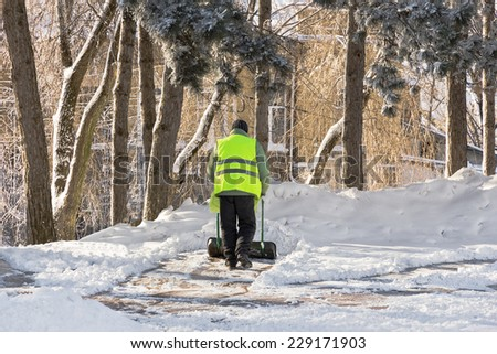 Worker in bright green uniforms removes snow in the city park. - stock photo