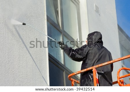 worker in cherry-picker washing a wall - stock photo