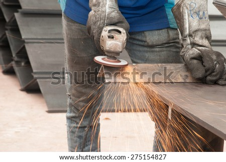 worker in constructing industry grinding metal - stock photo