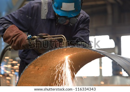 worker in factory cutting steel pipe using metal torch - stock photo