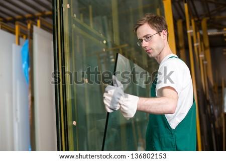Worker in glazier's workshop, warehouse  or storage handling glass - stock photo