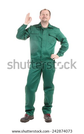 Worker in green with ok sign. Isolated on a white background. - stock photo