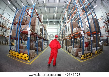 Worker in hard hat and red uniform in warehouse - back view - stock photo