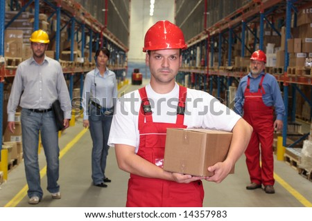 worker in hardhat with parcel at the front of team of workforce in warehouse - stock photo