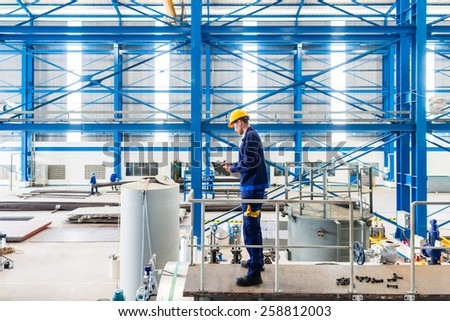 Worker in large metal workshop or factory checking work standing on large machine - stock photo