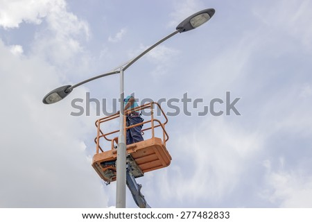 worker in lift bucket repair street light pole with double head - stock photo