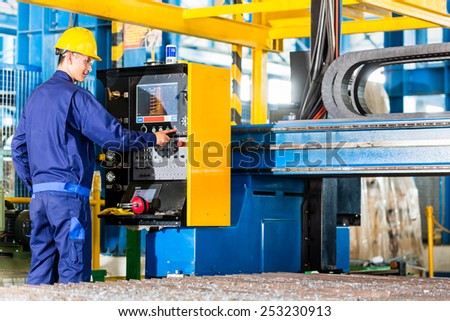 Worker in manufacturing plant at CNC machine control panel - stock photo
