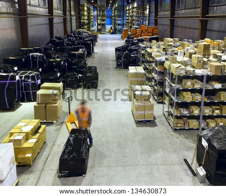 Worker in motion on forklift in large modern warehouse - stock photo