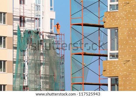 Worker in orange clothes stands on scaffolding of high-rise buildings under construction at sunny day. - stock photo