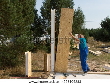 Worker in overalls standing erecting insulated wooden wall panels on a building site of a new house - stock photo