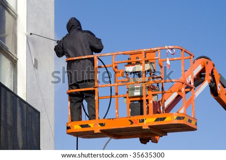 Worker In Platform Washing Building - stock photo