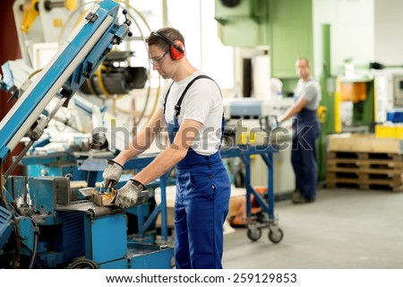 worker in protective clothing in factory using machine - stock photo