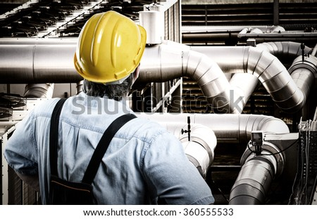 Worker in protective uniform and protective helmet in front of industrial pipes - toned image, retro film filtered in instagram style - stock photo
