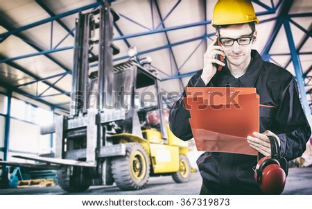 Worker in protective uniform in production hall in front of forklift - toned image, retro film filtered in instagram style - stock photo