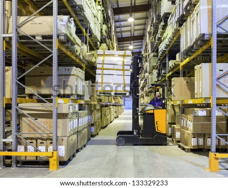 Worker in the motion on forklift in the large modern warehouse - stock photo