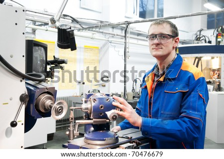 worker in uniform and protective glasses sharpen countersink reamer at machine tool - stock photo
