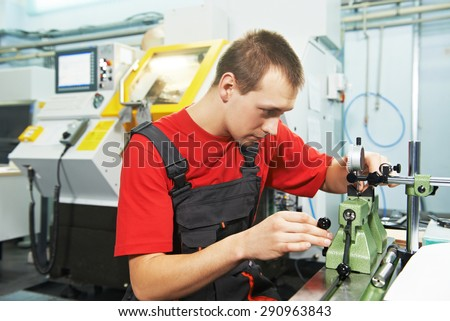 worker in uniform checking quality of processed tool using precise optical device - stock photo