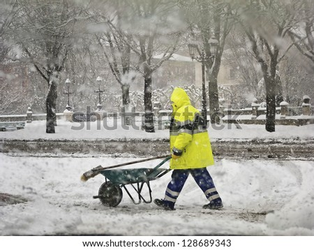 Worker in uniform removing snow in winter snowstorm. - stock photo
