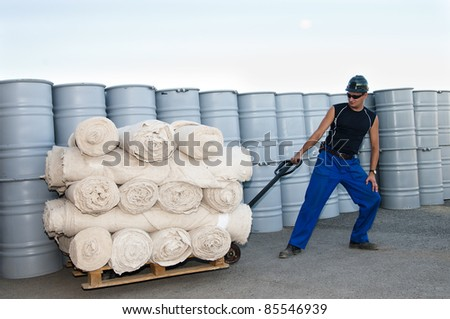 worker in warehouse transportation fabric rolls - stock photo