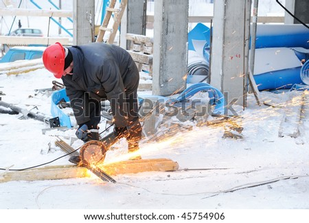 worker in workwear cutting metal reinforcing bar with abrasive cutoff saw disk - stock photo