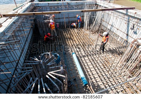 worker in workwear making reinforcement metal framework for concrete pouring. - stock photo