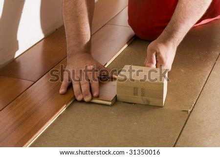 worker install a hardwood floor - stock photo