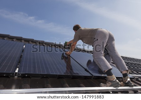 worker installing alternative energy photovoltaic solar panels. - stock photo