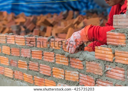 Worker installing red brick for construction site,bricklayer laying bricks to make a wall in construction site, - stock photo