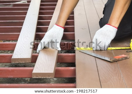 Worker installing wood floor for patio - stock photo