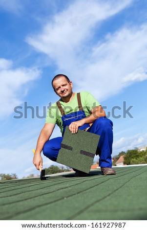 Worker installs bitumen roof shingles on top of building - stock photo