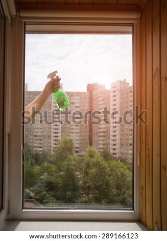 Worker is cleaning window glass sunny day - stock photo