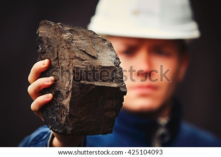 Worker is showing lignite - often referred to as brown coal - stock photo