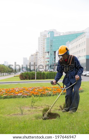 Worker landscaper mowing grass with power tool string lawn trimmer near city building - stock photo