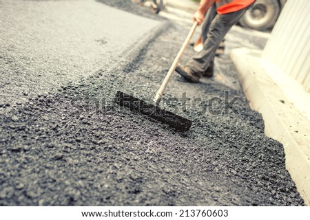 Worker leveling fresh asphalt on a road construction site, industrial buildings and teamwork. Vintage effect - stock photo