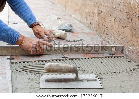 worker leveling new pavement with a specific tool. - stock photo