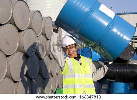 worker lifting drum on warehouse - stock photo