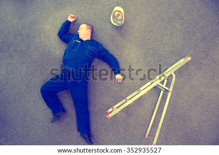 worker lying on the ground - accident at work - stock photo