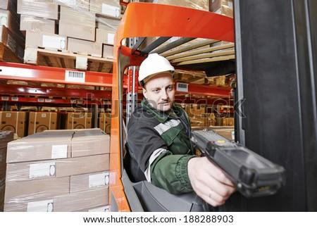 worker man in uniform scanning package in modern warehouse - stock photo