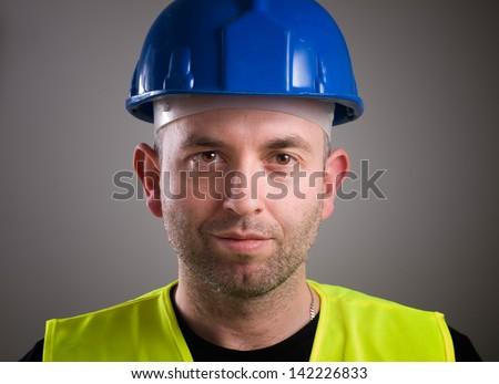 Worker man portrait isolated on dark background - stock photo