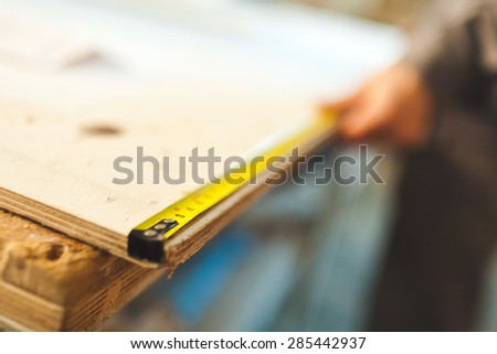 Worker measures wooden deck with tape measure in workshop. Selective focus photo - stock photo