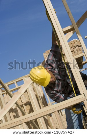 Worker measuring formwork at construction site - stock photo