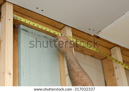 Worker Measuring Frame for Insulation - stock photo