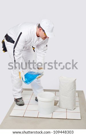 Worker mix tile adhesive in bucket of water with product package - stock photo